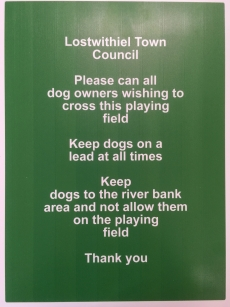 Sign: Lostwithiel Town Council, Please can all dog owners wishing to cross this playing field, Keep dogs on leads at all times, Keep dogs to the river bank area and not allow them on the playing field, Thank you