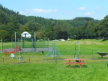 Play area with skate park in background